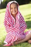 Muchacha envuelta en la toalla que se sienta en jardín Imagenes de archivo