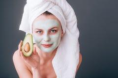 Muchacha envuelta en una toalla con una máscara cosmética en su cara y aguacate en sus manos imágenes de archivo libres de regalías