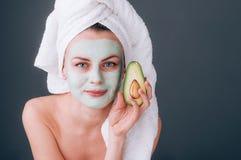 Muchacha envuelta en una toalla con una máscara cosmética en su cara y aguacate en sus manos imagen de archivo