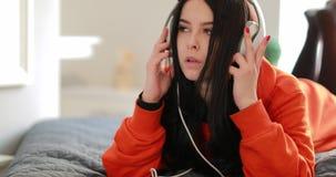 Muchacha escuchando la música en los auriculares grandes en casa que mienten en el sofá almacen de video
