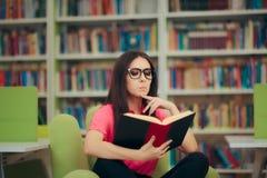 Muchacha estudiosa que lee un libro en una biblioteca Imágenes de archivo libres de regalías