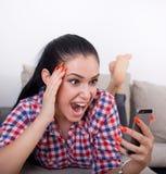 Muchacha eufórica con el teléfono móvil en el sofá Imagen de archivo libre de regalías