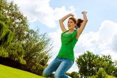 Muchacha eufórica que salta en parque. Fotografía de archivo libre de regalías
