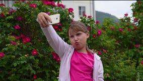 Muchacha europea con el pelo rubio que toma imágenes de sí misma en su smartphone almacen de metraje de vídeo