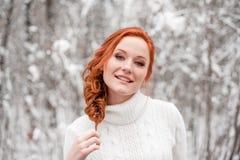 Muchacha europea del jengibre en el suéter blanco en la nieve diciembre del bosque del invierno en parque Tiempo maravilloso de l Imagenes de archivo