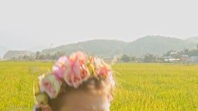 Muchacha europea en Garland Walks Smells Rose Sits abajo en hierba metrajes