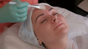Muchacha europea hermosa con los ojos cerrados en el procedimiento en el salón de belleza Manos del cosmetólogo en los guantes ve almacen de metraje de vídeo