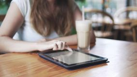 Muchacha europea hermosa joven que usa la tableta en un café en día de verano caliente con de la leche y del café, cierre el cóct metrajes