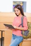 Muchacha excelente joven del estudiante que trabaja con la tableta Imágenes de archivo libres de regalías