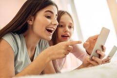 Muchacha extática que atrae su atención de los amigos a los posts en línea Foto de archivo