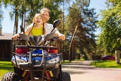 Muchacha exuberante que conduce ATV con su papá Fotografía de archivo