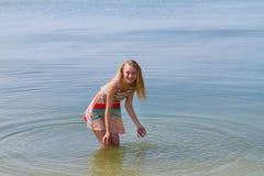 Muchacha feliz adolescente en el vestido colorido que presenta en el mar Imagenes de archivo