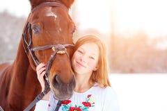 Muchacha feliz adolescente joven con el caballo en parque del invierno Fotografía de archivo