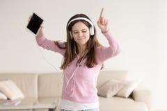 Muchacha feliz adolescente que escucha la música en auriculares y el baile Fotografía de archivo libre de regalías
