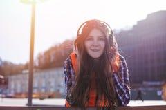 Muchacha feliz adolescente que escucha la música en el parque de la ciudad al aire libre Fotos de archivo