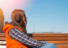 Muchacha feliz adolescente que escucha la música en el parque de la ciudad al aire libre Imagen de archivo