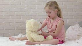 Muchacha feliz adorable del pequeño niño que juega con el oso de peluche metrajes