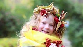 Muchacha feliz alegre con una guirnalda en su ceniza de montaña principal en el bosque del otoño almacen de video