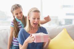 Muchacha feliz asombrosamente su madre con el regalo en casa Imagenes de archivo
