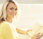 Muchacha feliz atractiva con un libro en casa Imagen de archivo libre de regalías