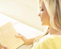 Muchacha feliz atractiva con un libro en casa Fotos de archivo
