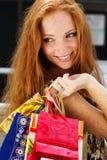 Muchacha feliz atractiva hacia fuera que hace compras Imagen de archivo