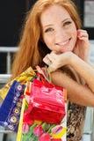 Muchacha feliz atractiva hacia fuera que hace compras Foto de archivo libre de regalías
