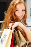 Muchacha feliz atractiva hacia fuera que hace compras Fotos de archivo