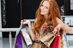 Muchacha feliz atractiva hacia fuera que hace compras Foto de archivo