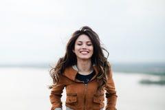 Muchacha feliz atractiva joven con el pelo largo que sonríe y que presenta al aire libre El viento sopla su pelo Imagenes de archivo