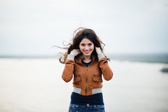 Muchacha feliz atractiva joven con el pelo largo que sonríe y que presenta al aire libre El viento sopla su pelo Fotografía de archivo