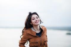 Muchacha feliz atractiva joven con el pelo largo que sonríe y que presenta al aire libre El viento sopla su pelo Fotos de archivo libres de regalías