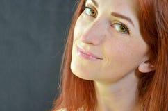 Muchacha feliz blanca con el pelo rojo y los ojos verdes con extensiones de la pestaña en el fondo gris que mira adelante fotografía de archivo libre de regalías