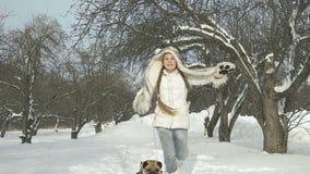 Muchacha feliz a cámara lenta que juega con su perro en nieve y que se divierte fuera del día de invierno almacen de metraje de vídeo