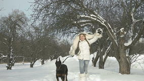 Muchacha feliz a cámara lenta que juega con su perro en nieve y que se divierte fuera del día de invierno metrajes