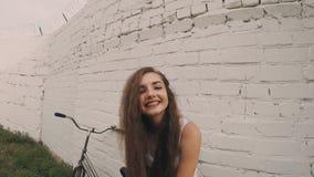 Muchacha feliz cerca de la pared blanca, tiro retro del color Mujer joven que presenta cerca de la pared que se inclina del bycic metrajes