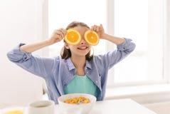 Muchacha feliz con anaranjado desayunando en casa Imagen de archivo libre de regalías