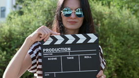 Muchacha feliz con día de verano ventoso de la tablilla en a almacen de video