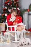 Muchacha feliz con dos golden retriever de los perritos en un fondo del árbol de navidad Foto de archivo libre de regalías
