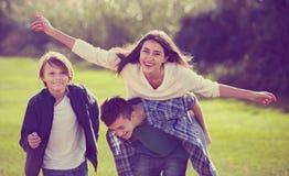 Muchacha feliz con dos muchachos que presentan en parque de la caída Fotografía de archivo libre de regalías