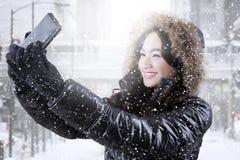 Muchacha feliz con el abrigo de invierno que toma el selfie Imagenes de archivo