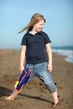 Muchacha feliz con el arma del juguete en la playa Foto de archivo