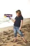 Muchacha feliz con el arma del juguete en la playa Foto de archivo libre de regalías