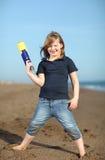 Muchacha feliz con el arma del juguete en la playa Imagenes de archivo