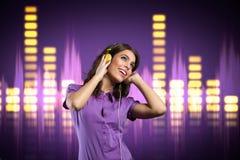 Muchacha feliz con el auricular que escucha la música Imagenes de archivo