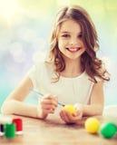 Muchacha feliz con el cepillo que colorea los huevos de Pascua Fotos de archivo libres de regalías