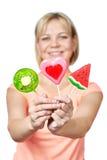 Muchacha feliz con el corazón de la piruleta, la sandía y la fruta de kiwi Foto de archivo