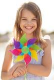 Muchacha feliz con el juguete colorido del molinillo de viento Imágenes de archivo libres de regalías