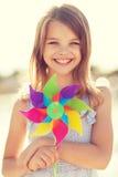 Muchacha feliz con el juguete colorido del molinillo de viento Foto de archivo