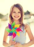 Muchacha feliz con el juguete colorido del molinillo de viento Fotos de archivo libres de regalías